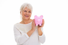 Senior woman holding piggy bank. Over white background Royalty Free Stock Photography