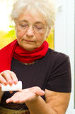 Senior woman holding a pill in her hand Stock Image