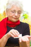 Senior woman holding a pill in her hand Stock Photo