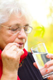 Senior woman holding a pill in her hand Stock Photos