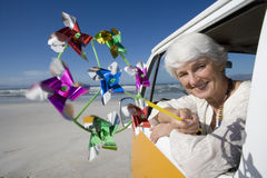 Senior woman holding pinwheel out window of camper van on beach, smiling, portrait Royalty Free Stock Photos