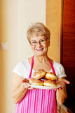 Senior woman holding plate with donuts Royalty Free Stock Image