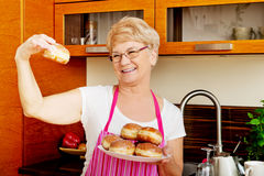 Senior woman holding plate with donuts Stock Photo