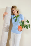 Senior woman holding pot plant and rolled up carpet, moving house, smiling, front view, portrait royalty free stock photos
