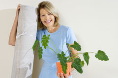 Senior woman holding pot plant and rolled up carpet, moving house, smiling, front view, portrait Royalty Free Stock Images