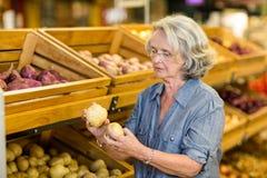 Senior woman holding potatoes Stock Photos