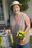 Senior Woman Holding Pruner And Flower Pot Royalty Free Stock Image