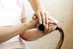 Close up of mature womans & nurse hands. Health care giving, nursing home. Parental love of grandmother. Old age related diseases. Senior woman holding quad royalty free stock photos