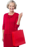 Senior woman holding red shopping bag Royalty Free Stock Photography