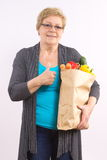 Senior woman holding shopping bag with fruits and vegetables and showing thumbs up, healthy nutrition in old age Stock Image
