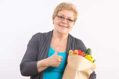 Senior woman holding shopping bag and showing thumbs up, healthy nutrition in old age Stock Photos