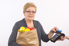 Senior woman holding shopping bag and using payment terminal with contactless credit card, paying for shopping Stock Photography