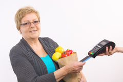 Senior woman holding shopping bag and using payment terminal with credit card, cashless paying for shopping Stock Image