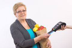 Senior woman holding shopping bag and using payment terminal with credit card, cashless paying for shopping Stock Photography