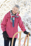 Senior Woman Holding Sledge In Snowy Landscape. Smiling At Camera Royalty Free Stock Images