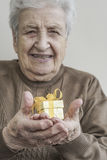 Senior woman holding a small gift Stock Photo