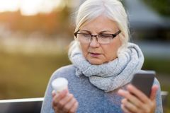 Woman holding smartphone and pill bottle. Senior woman holding smartphone and pill bottle stock photography