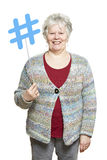 Senior woman holding a social media sign smiling. On white background Royalty Free Stock Images