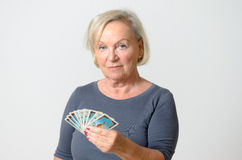 Senior Woman Holding Tarot Cards Against Gray Wall Stock Images
