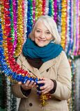 Senior Woman Holding Tinsels At Christmas Store Royalty Free Stock Image