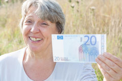 Senior woman holding twenty euro Royalty Free Stock Image