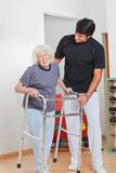 Senior Woman Holding Walker While Trainer Stock Photos