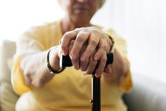 Senior woman holding a walking stick royalty free stock photos