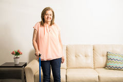 Senior woman holding walking stick for support. Pretty aged granny using a blue singlestick to stand up comfortable and be able to walk at home Royalty Free Stock Photography