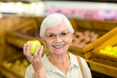Senior woman holding and watching a green apple. In supermarket Royalty Free Stock Photography