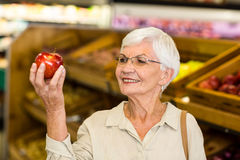 Senior woman holding and watching a red apple Royalty Free Stock Photo