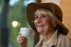 Senior woman holding white cup. Stock Photos