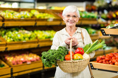 Senior woman holding wicker basket. In supermarket Royalty Free Stock Photos