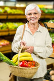 Senior woman holding wicker basket Royalty Free Stock Photos