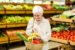 Senior woman holding wicker basket. In supermarket Stock Image