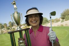 Senior Woman Holding Winning Trophy. Portrait of a happy senior women holding winning trophy at golf course Royalty Free Stock Photography