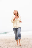 Senior Woman On Holiday Running Along Beach Royalty Free Stock Photos