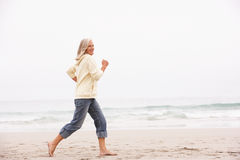 Senior Woman On Holiday Running Along Beach Stock Photo