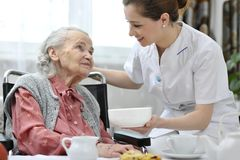 Senior woman with home caregiver stock images