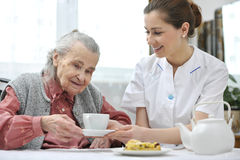 Senior woman with home caregiver. Senior women eats lunch at retirement home Royalty Free Stock Photos