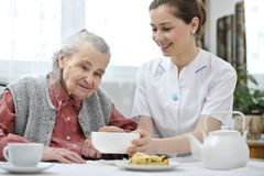 Senior woman with home caregiver. Senior women eats lunch at retirement home Stock Photography