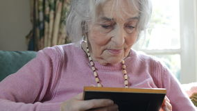 Senior Woman At Home Looking At Photo In Frame stock video