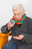 Senior woman at home. Picture of a senior woman sitting in her apartment and holding pills Royalty Free Stock Image