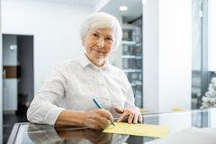 Senior woman at the hospital reception. Beautiful senior woman signing some medical documents stannding at the hospital reception stock photography