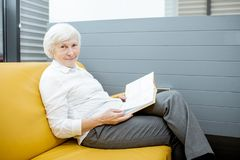 Senior woman at the hospital reception. Portrait of a beautiful senior woman waiting on the couch at the hospital reception stock images