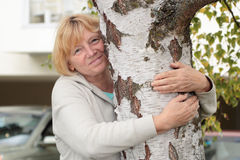 Senior woman hugging birch tree Stock Photo