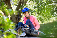 Senior woman is hurting because of her bike Royalty Free Stock Images