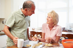 Senior Woman With Husband Baking Cookies In Kitchen Stock Photo