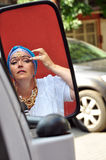 Senior woman with Indian jewlery looking at car mirrow in the s. Portrait of a beautiful blond senior woman with Indian necklace, earrings and tikka looking at royalty free stock image
