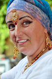 Senior woman with Indian jewlery in the street. Portrait of a beautiful blond senior woman with Indian necklace, earrings and tikka in the street royalty free stock photo