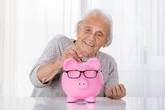 Senior Woman Inserting Coin In Piggybank Stock Photo